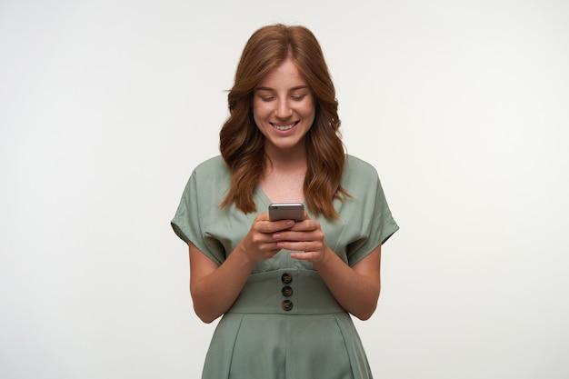 Foto interna de uma linda jovem com um vestido romântico segurando o smartphone nas mãos, olhando para a tela e sorrindo alegremente, isolada