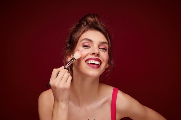 Foto interna de uma linda jovem de cabelos castanhos com penteado casual olhando positivamente no espelho e aplicando maquiagem com pincel, preparando-se para sair, isolado