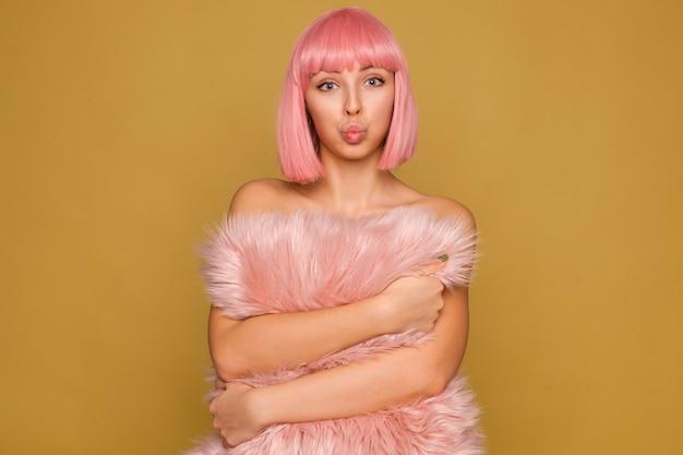 Foto interna de uma linda jovem de cabelos rosa de olhos azuis fazendo beicinho com os lábios enquanto olha com entusiasmo, mantendo o travesseiro fofo nas mãos enquanto fica de pé sobre a parede de mostarda