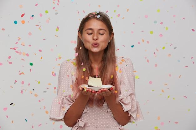Foto interna de uma linda jovem loira de cabelos compridos apagando a vela no bolo de aniversário em pé sobre uma parede branca, vestida com um vestido rosa romântico