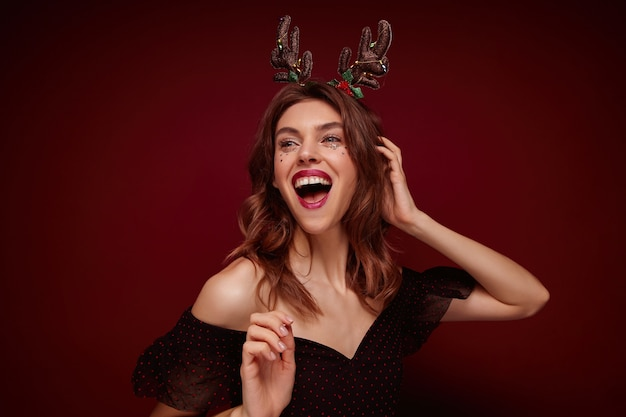 Foto interna de uma linda jovem morena alegre com penteado festivo, usando chifres de natal e roupas elegantes enquanto posa, expressando verdadeiras emoções positivas