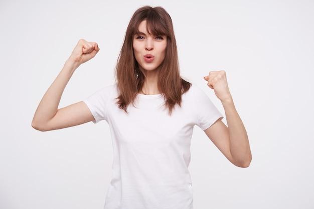 Foto interna de uma linda jovem morena com maquiagem natural, levantando os punhos enquanto olha animadamente, vestindo uma camiseta branca básica enquanto posa sobre uma parede branca