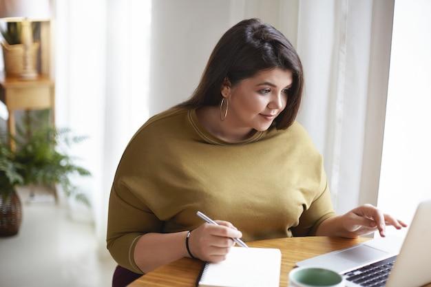 Foto interna de uma linda jovem morena com sobrepeso plus size em roupas elegantes, sentada à mesa com o laptop aberto, uma caneca de café e anotando informações em seu diário, estudando online