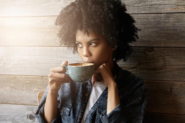Foto interna de uma linda mulher afro-americana com penteado afro segurando uma caneca grande