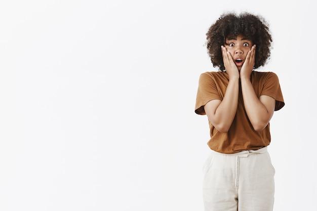 Foto interna de uma linda mulher afro-americana sentindo empatia e choque de mãos dadas no rosto, arfando com a boca aberta e olhando atordoada por estar impressionada depois de ouvir más notícias
