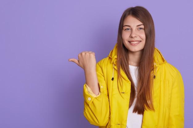 Foto interna de uma linda mulher com cabelo comprido aponta com o polegar de lado, vestida de jaqueta amarela casual, mostra algo isolado sobre fundo lilás.