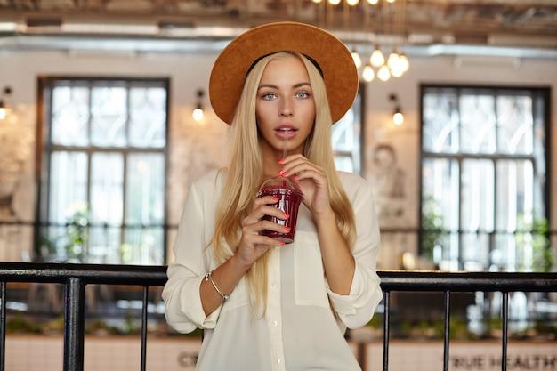 Foto interna de uma linda mulher loira de cabelos compridos com olhos azuis posando sobre o interior do restaurante, bebendo limonada com canudo, usando chapéu e camisa