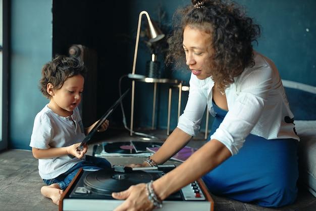 Foto interna de uma linda mulher melomaníaca de raça mista, sentada no chão com seu filho, usando um toca-discos, ouvindo música juntos