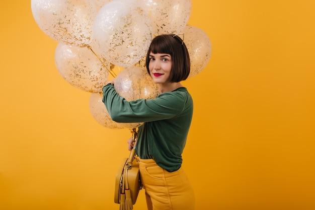 Foto interna de uma linda senhora caucasiana comemorando aniversário. retrato de uma incrível garota de cabelos castanhos em pé de camisola verde com balões.