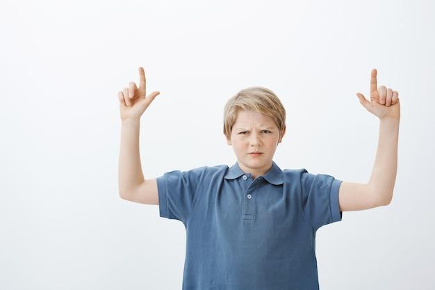 Foto interna de uma loira insatisfeita e insatisfeita com uma criança de camiseta azul, franzindo a testa e levantando o dedo indicador enquanto aponta para cima