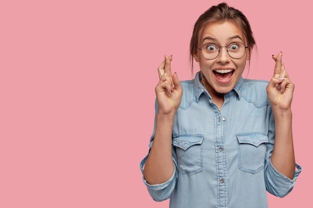 Foto interna de uma modelo feminina alegre com expressão animada, mantendo os dedos cruzados