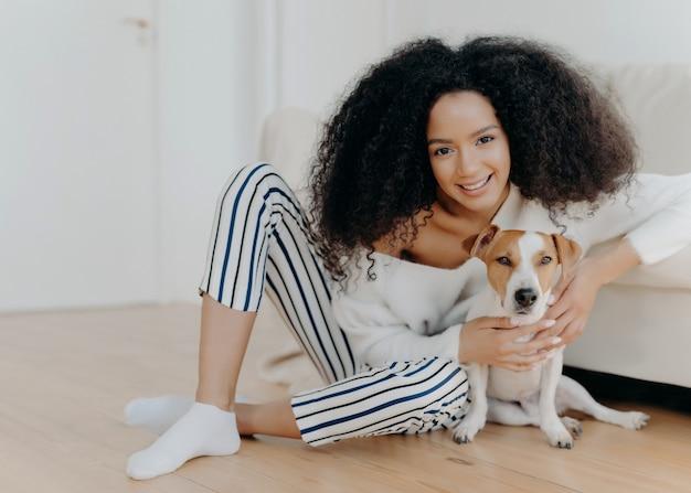 Foto interna de uma modelo feminina de cabelo encaracolado satisfeita posa para a foto com o cachorro jack russell terrier, abraça o animal de estimação com ternura, senta-se no chão com o animal amado perto de um sofá confortável, passe um tempo juntos