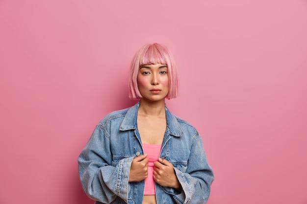 Foto interna de uma modelo feminina séria de cabelo rosa, vestida com uma jaqueta jeans enorme e uma aparência direta, usando o mínimo de maquiagem,