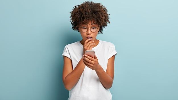 Foto interna de uma mulher afro-americana atordoada focada em um telefone celular, lendo notícias terríveis e impressionantes, usando um aplicativo moderno, usando óculos para correção de visão isolado contra uma parede azul, chamada perdida