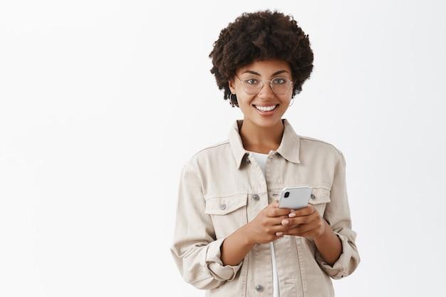 Foto interna de uma mulher afro-americana atraente, feliz e satisfeita usando um smartphone novinho em folha e olhando satisfeita, sorrindo sobre a parede cinza