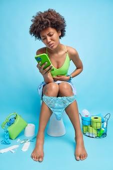 Foto interna de uma mulher afro-americana com cólicas abdominais durante pesquisas de constipação na internet que remédio tomar contém poses de celular no banheiro no vaso sanitário