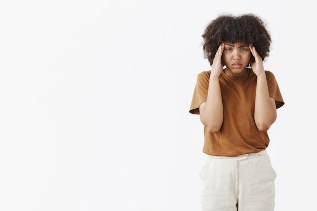 Foto interna de uma mulher afro-americana intensa e incomodada com um penteado afro encaracolado de mãos dadas nas têmporas, franzindo a testa e olhando com uma expressão doente e cansada tentando se concentrar
