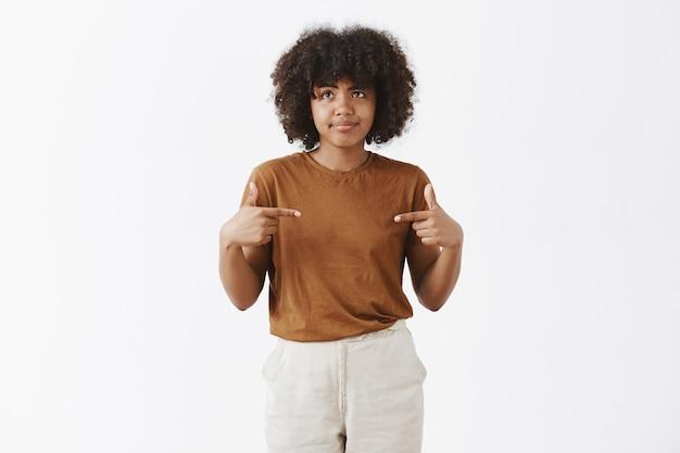 Foto interna de uma mulher afro-americana intensa infeliz e descontente sendo escolhida por alguém franzindo os lábios e sorrindo desapontada olhando para a esquerda apontando para si mesma