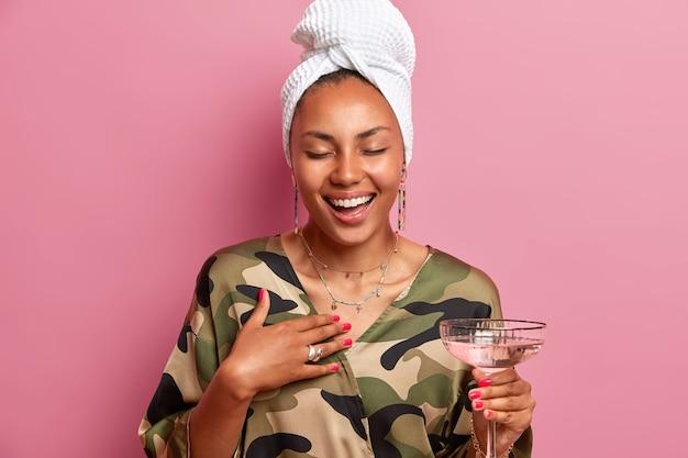 Foto interna de uma mulher afro-americana sorridente e satisfeita com pele escura e saudável fechando os olhos