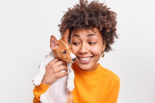 Foto interna de uma mulher amigável e um cachorro se divertem brincando juntos, têm bons relacionamentos, aproveitam o bom momento a dona do animal de estimação feminino positiva segura o pequeno cachorro conceito de animais e pessoas.