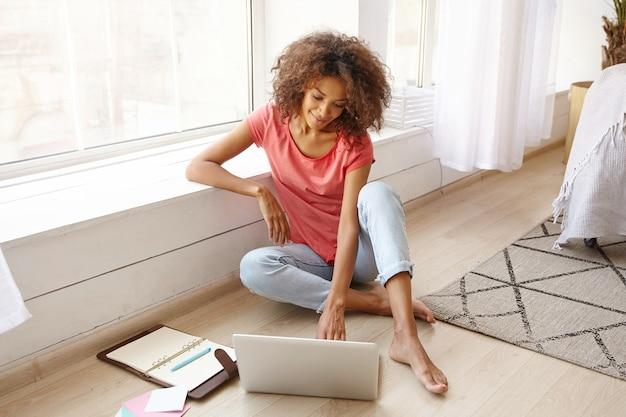 Foto interna de uma mulher atraente de pele escura encostada no parapeito da janela enquanto está sentada no chão, trabalhando remotamente de casa com um laptop e notebook modernos, emoções positivas