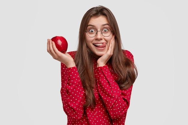 Foto interna de uma mulher atraente lambendo os lábios enquanto segura uma maçã fresca e suculenta, se diverte, se veste com elegância, gosta de comer vitaminas