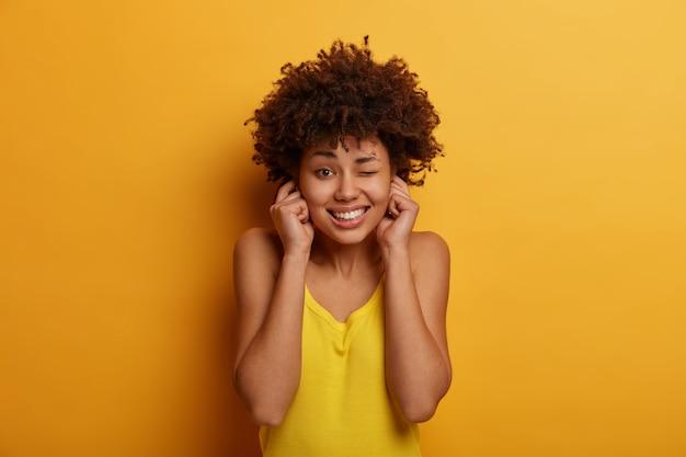 Foto interna de uma mulher bonita tapa os ouvidos, evita música muito alta na festa, pisca os olhos, cerra os dentes, vestida com roupas amarelas, posa dentro de casa, não consegue ouvir barulho, evita vizinhos muito barulhentos