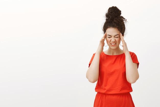 Foto interna de uma mulher caucasiana infeliz em um vestido vermelho, fechando os olhos e fazendo uma careta de dor, segurando os dedos nas têmporas