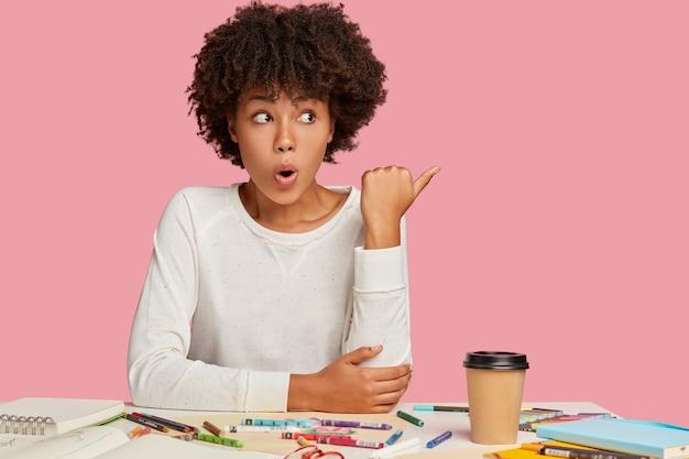 Foto interna de uma mulher chocada e surpresa com expressão facial estupefata, senta-se à mesa com o papel de parede necessário, bebe bebida fresca, aponta para o espaço livre com o polegar, nota algo horrível