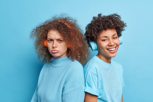 Foto interna de uma mulher de cabelo encaracolado descontente e seu melhor amigo companheiro, um de costas para o outro, ouvindo música em fones de ouvido sem fio isolados sobre a parede azul. diversas mulheres posam de perto