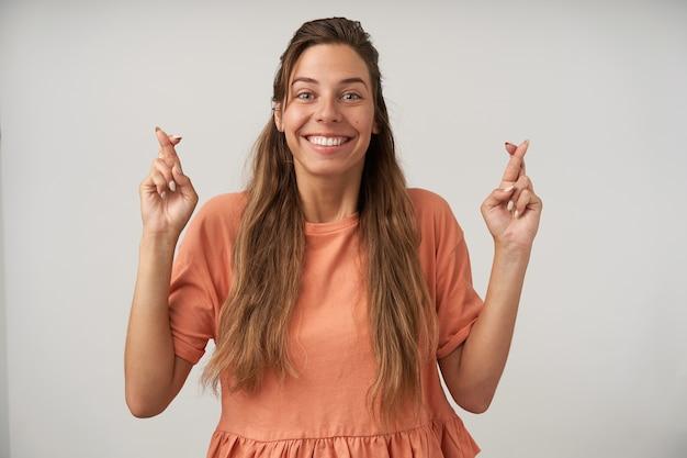Foto interna de uma mulher de cabelos compridos de aparência agradável com penteado casual, cruzando os dedos e com grande esperança de melhorar, usando uma camiseta cor de pêssego