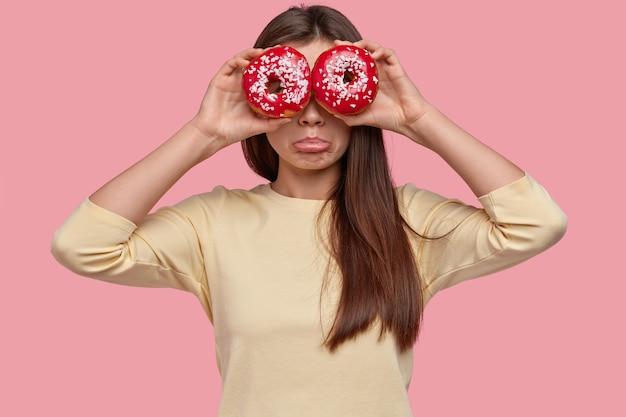 Foto interna de uma mulher de cabelos escuros descontente cobre os olhos com donuts e franze os lábios em insatisfação