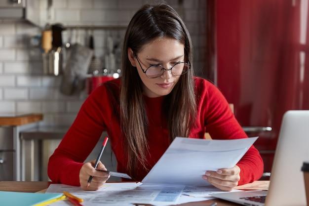 Foto interna de uma mulher de óculos ópticos verifica a conta bancária, recebe contas, segura um cartão de plástico
