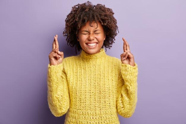 Foto interna de uma mulher de pele escura feliz e positiva deseja o melhor, cruza os dedos, sorri amplamente, tem os olhos fechados, mostra dentes brancos perfeitos, usa um macacão amarelo e espera por um momento especial. que os sonhos se tornem realidade