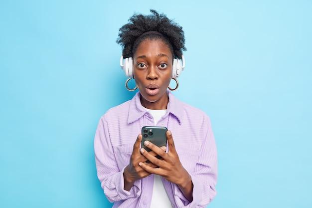 Foto interna de uma mulher de pele escura surpresa segurando um celular ouvindo música com fones de ouvido