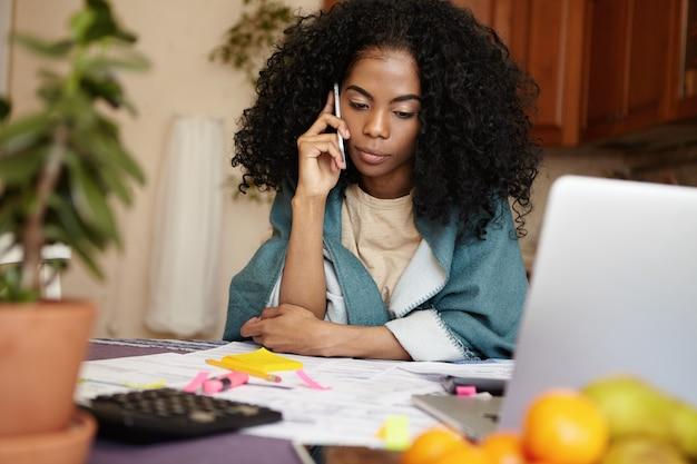 Foto interna de uma mulher desempregada de pele escura conversando ao telefone com a amiga, pedindo dinheiro para pagar dívidas, sentada à mesa da cozinha com um laptop e documentos, calculando contas