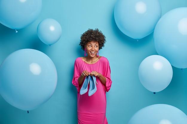 Foto interna de uma mulher elegante e alegre com cabelo afro, vestida com um vestido rosa, segura sapatos de salto alto, se prepara para a festa de aniversário, tenta escolher o que vestir, olha de lado, balões azuis ao redor