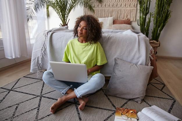Foto interna de uma mulher encaracolada de pele muito escura em roupas casuais, olhando para o lado com um rosto satisfeito, sentada no tapete do quarto, segurando o laptop nas pernas