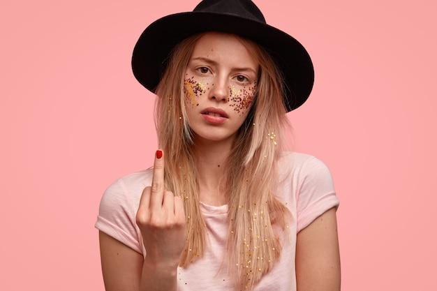 Foto interna de uma mulher europeia bonita e brutal mostra o dedo médio, mostra sua antipatia ou descontentamento com algo, usa chapéu preto e camiseta casual