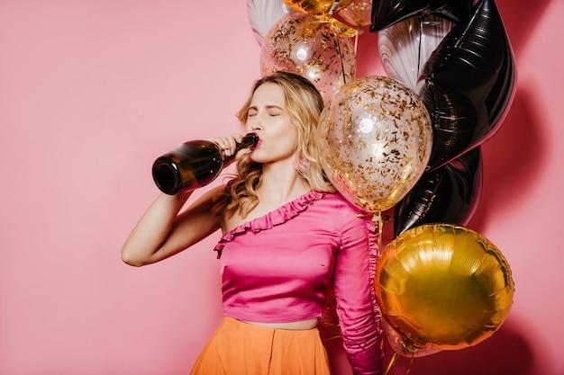 Foto interna de uma mulher europeia com cabelo loiro bebendo vinho
