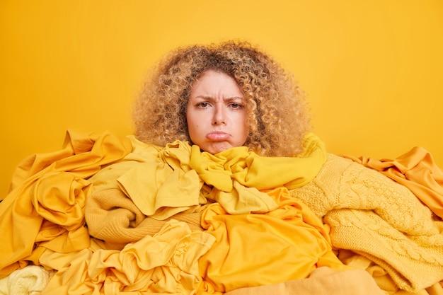 Foto interna de uma mulher européia de cabelos cacheados chateada cercada por roupas desordenadas com bolsas de roupas. os lábios têm uma expressão de rosto frustrada isolada sobre o amarelo