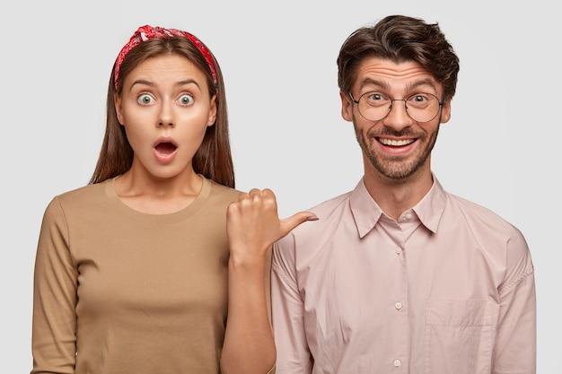 Foto interna de uma mulher europeia surpresa apontando com o polegar para seu companheiro alegre
