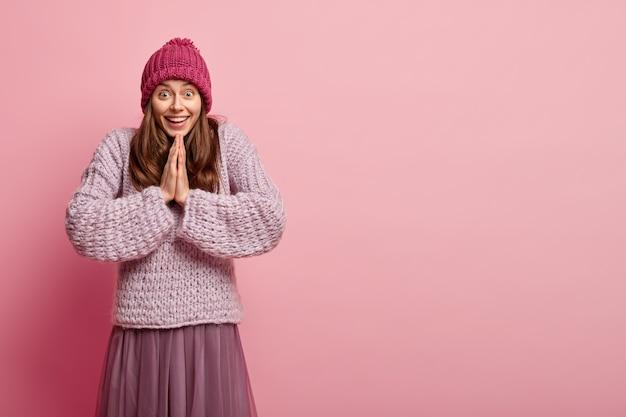 Foto interna de uma mulher feliz e satisfeita mantém as palmas das mãos pressionadas, reza e espera pelo melhor, tem expressão facial alegre, vestida com roupas quentes da moda, fica sobre uma parede rosa com espaço livre