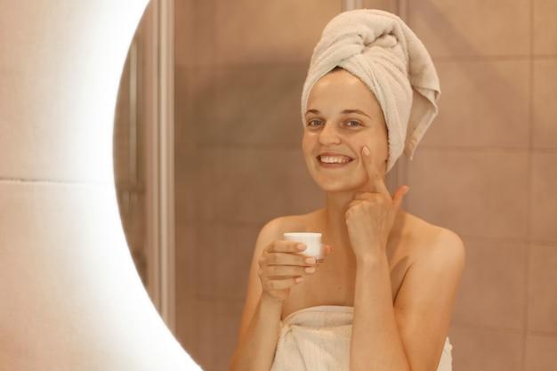 Foto interna de uma mulher feliz e sorridente em frente ao espelho, esfregando creme cosmético no rosto, passando hidratante na pele do rosto no banheiro.