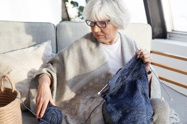 Foto interna de uma mulher idosa séria e concentrada, com cabelos grisalhos, sentada no sofá da sala de estar usando óculos, tricotando roupas quentes de inverno para seu site na internet, vendendo produtos caseiros online