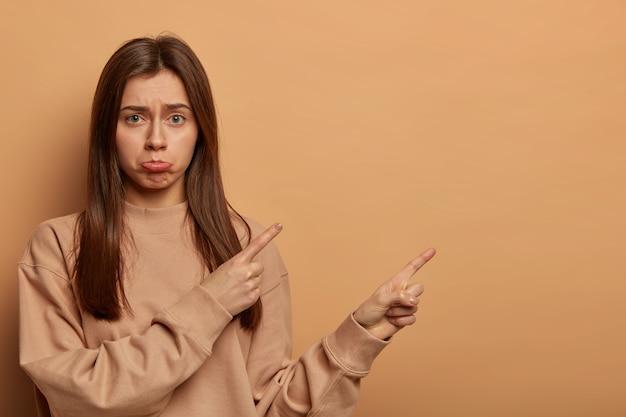 Foto interna de uma mulher infeliz e desapontada aponta para um espaço em branco, oportunidade perdida, pede sua opinião, faz uma escolha perplexa, franze o lábio inferior