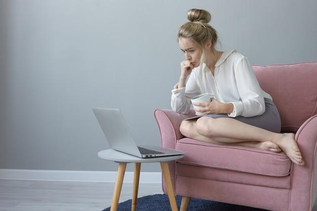 Foto interna de uma mulher jovem e atraente com coque de cabelo, sentada descalça em uma poltrona com uma xícara de café e assistindo a um webinar no computador laptop, aprendendo online, tendo um olhar concentrado