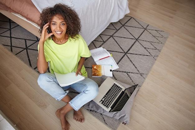 Foto interna de uma mulher jovem e atraente encaracolada com pele escura, encostada na cama e posando sobre o interior da casa, olhando animadamente, segurando uma caneta e um caderno