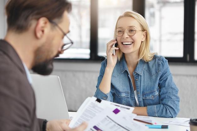 Foto interna de uma mulher loira conversando sobre negócios com um colega
