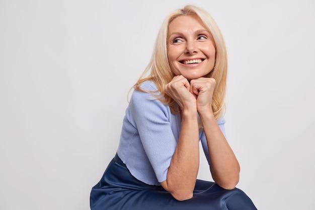 Foto interna de uma mulher loira de meia-idade sonhadora com as mãos embaixo do queixo traz uma lembrança agradável em mente com sorrisos largamente encostados na parede cinza